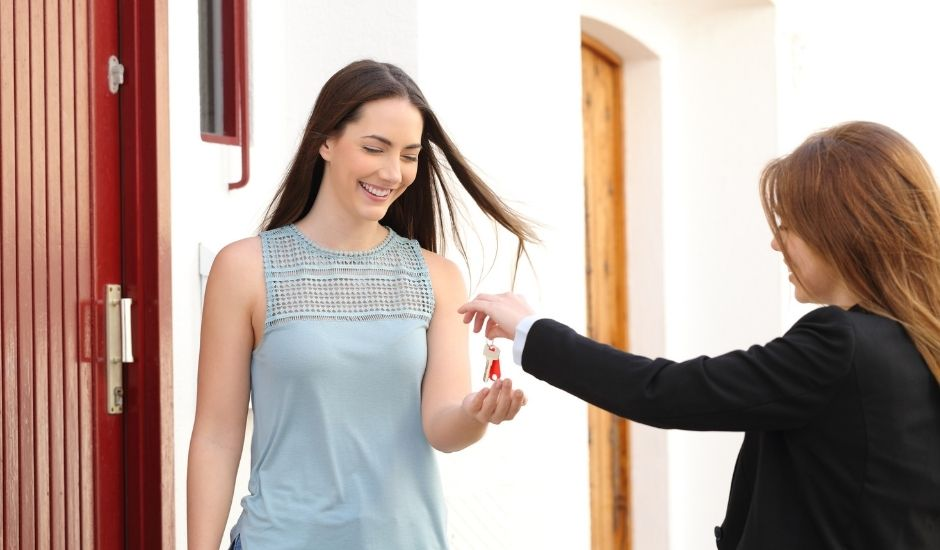 A young person receives house keys from a realtor.